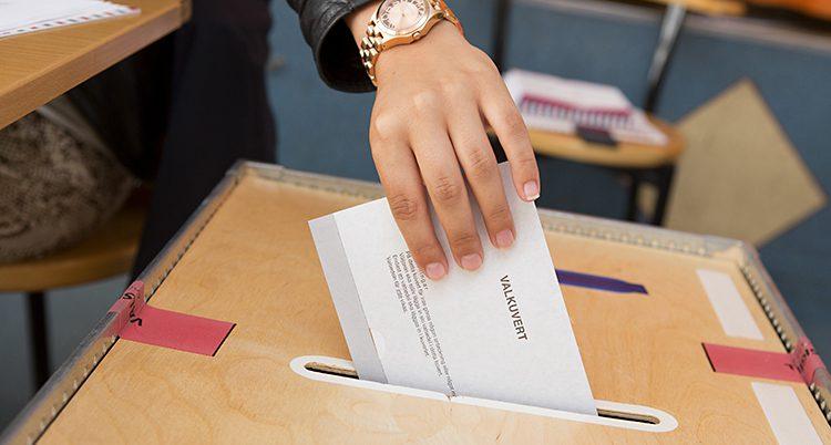 En person lägger ett valkuvert i en låda.