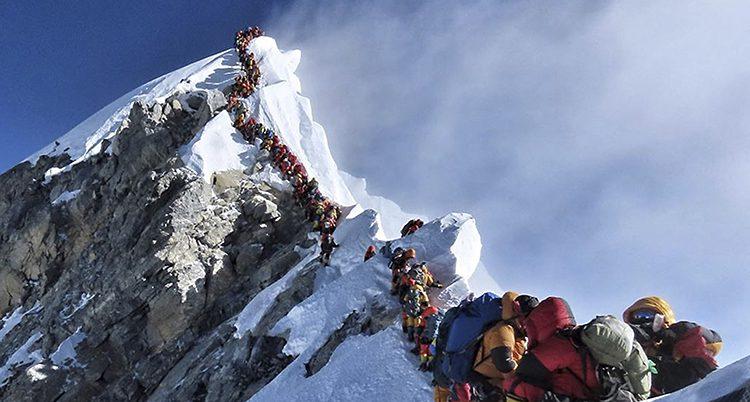 En lång kö med klättrare på en smal bergskam