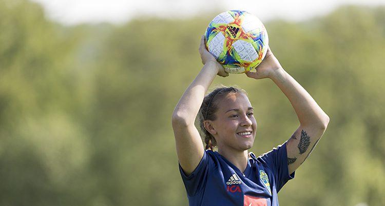 Julia håller bollen över huvudet och ska göra ett inkast. Hon ser glad ut.