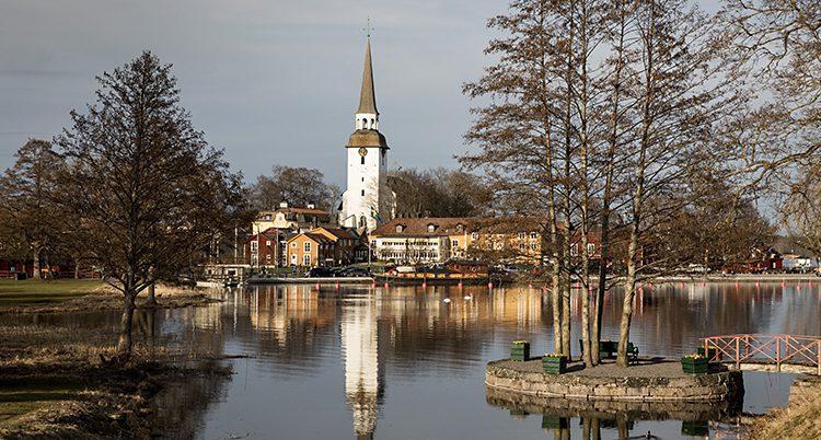 En kyrka vid en sjö. Tornet speglar sig i vattnet.
