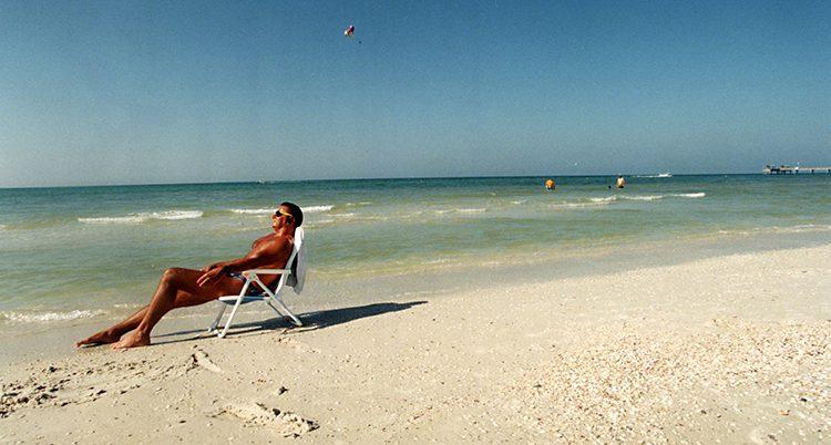 En solbränd man sitter och solar på en strand