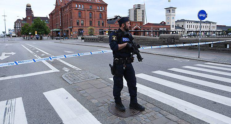 En polis med vapen stor på en gata utanför stationen