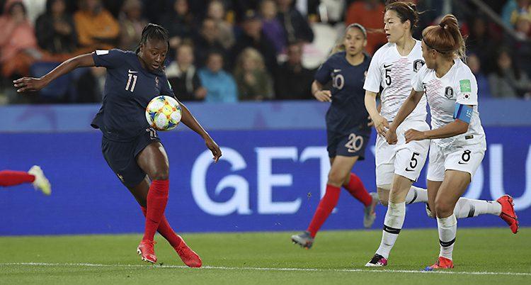 En fransk spelare tar emot bollen i luften. Två koreanskor är på väg att försöka stoppa henne