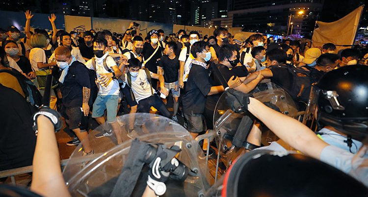 Trängsel framför poliser med sköldar. Folk försöker att fly
