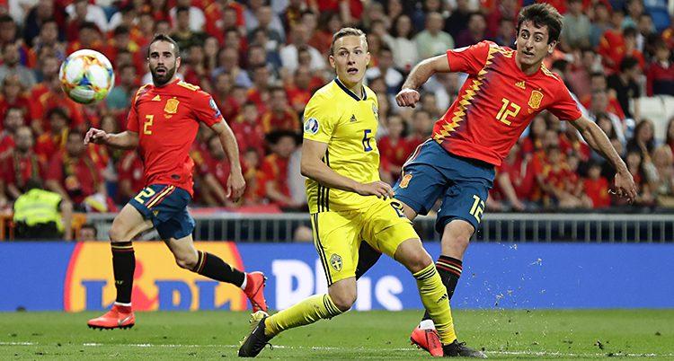 En spanjor skjuter och svensken tittar efter bollen.