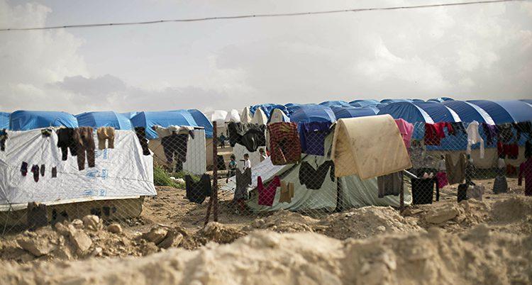 Sandig mark och tält. Framför tälten hänger sträck med kläder på tork.