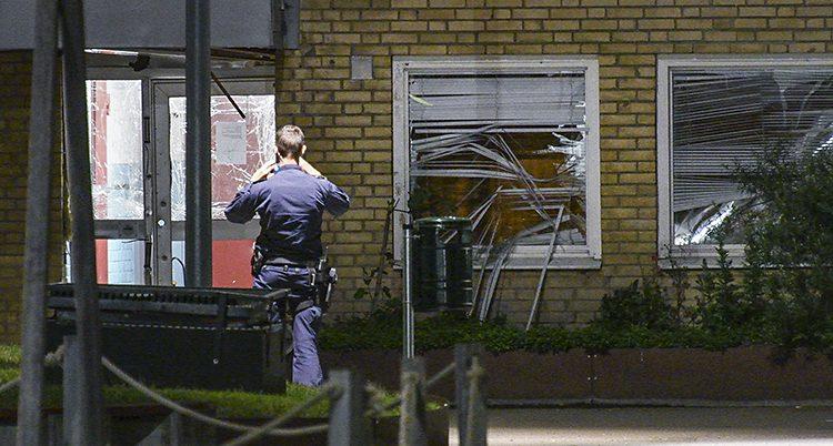 En polis står framför en port till ett tegelhus. Fönstret till entredörren är krossad. Likaså fönstret bredvid dörren.
