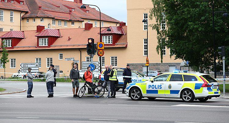 Polisbilar står i en gatan och stoppar människor