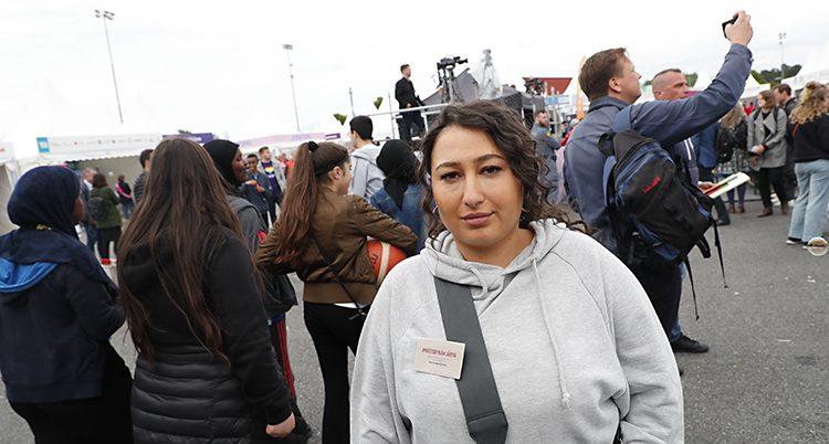 Eleni Terzitane står på en gata med många människor runt sig.