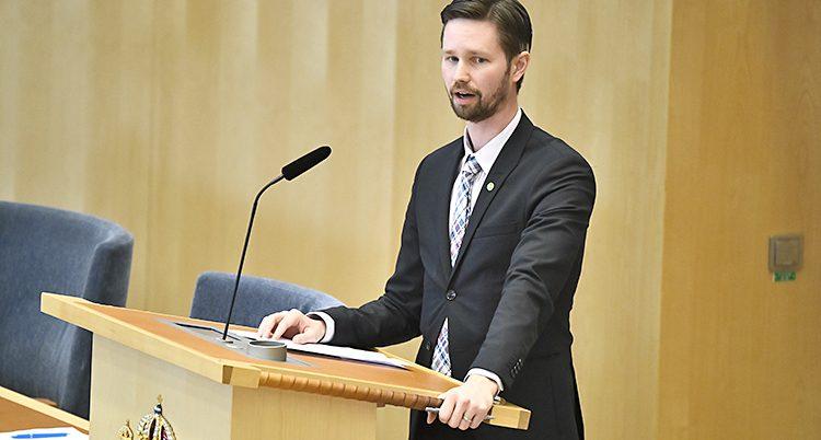 Politikern Rasmus Ling står vid en talarstol i riksdagen.