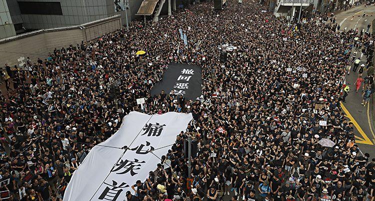 En gatan helt fylld av människor. En del av dem bär på ett stort tyg med bokstäver.