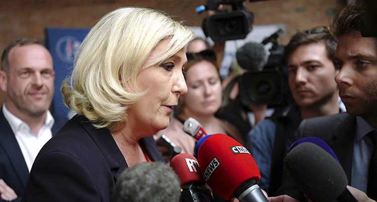 En kvinna imed blont hår pratar i flera mikrofoner