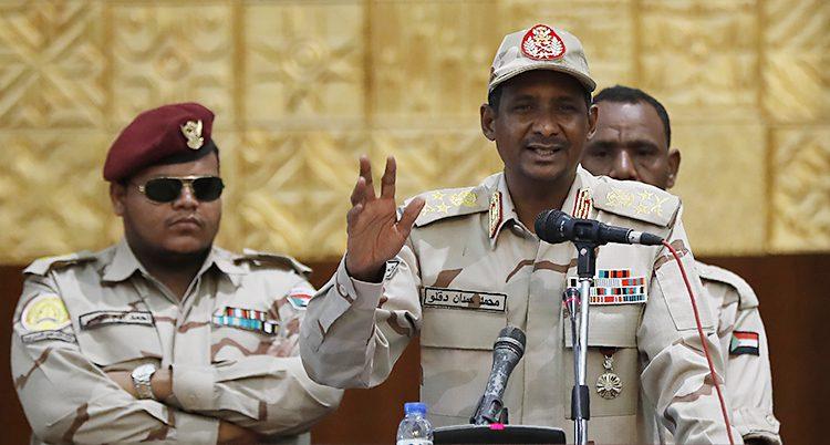En militär talar bakom honom stpår två amdra. Enm m,ed armarna i kors och solglasögon.