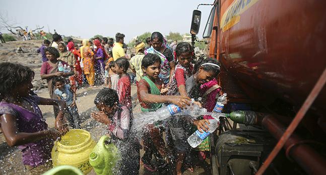 Barn fyller vattenflaskor. Det sprutar vatten på vägen där de står.