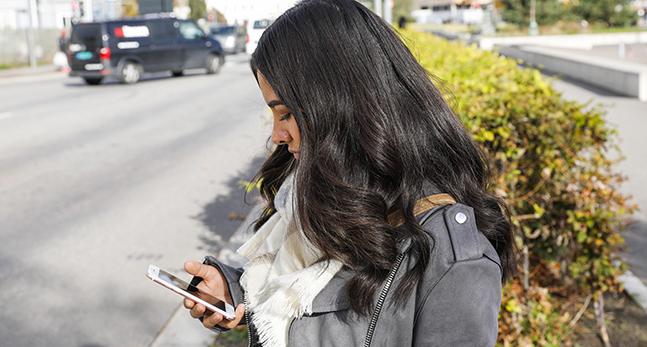 En flicka med en mobiltelefon i handen.