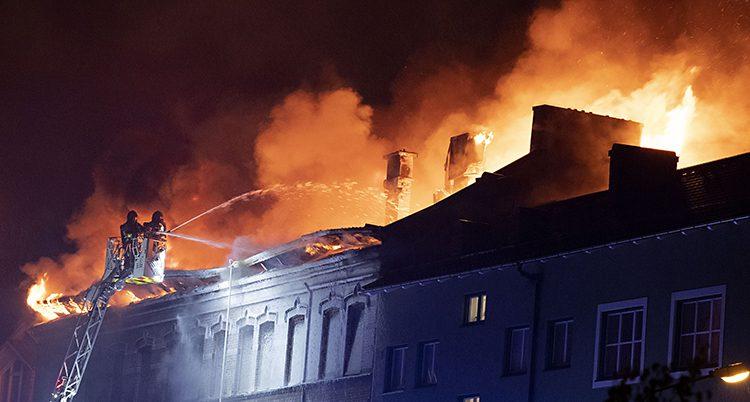 Brandmän i en korg högt uppe på en stegensprutar vatte över taget. Det brinner i taker. Det är mörkt och lågorna är orangea.