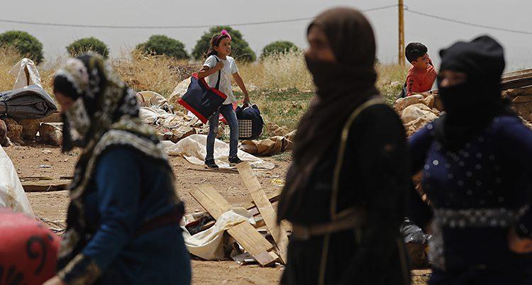 Kvinnor med sjalar över ansiktet i förgrunden. En flicka med en stor väska i bakgrunden.