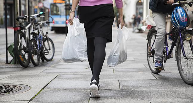 En kvinna i svart kjol och svarta strumbyxor bär en plastpåse i varje hand.
