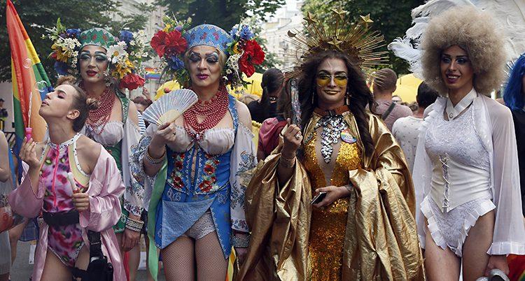 Människor i glittriga klänningar och en regnbågsflagga.