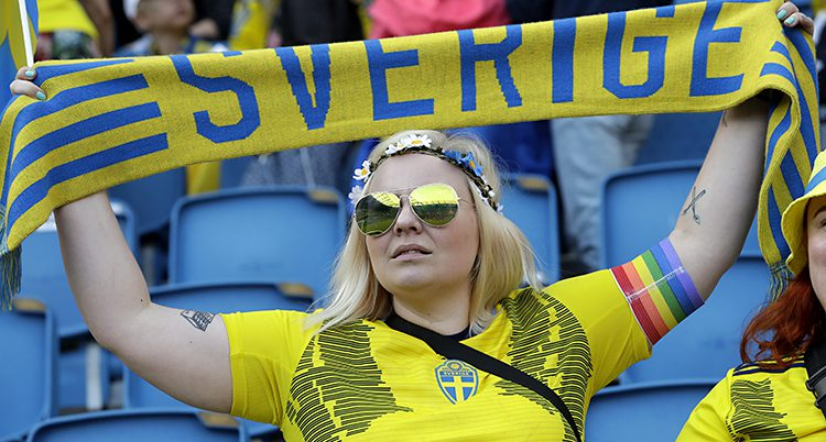 En kvinnlig supporter i svensk tröja håller upp en halsduk det står Sverige på.