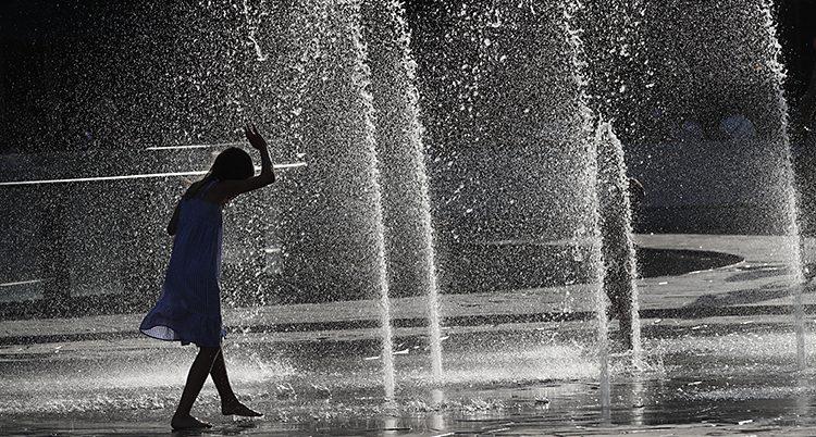 Flickan springer under flera höga strålar vatten i fontänen.