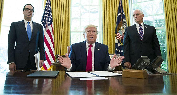 USAs president sitter bakom sitt skrivbord. På varsin sida har han en medhjälpare.