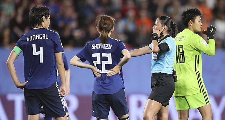 Några spelare står runt en domare på en fotbollsplan.