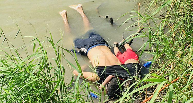 En man och en liten flicka ligger på magen vid stranden av en flod.