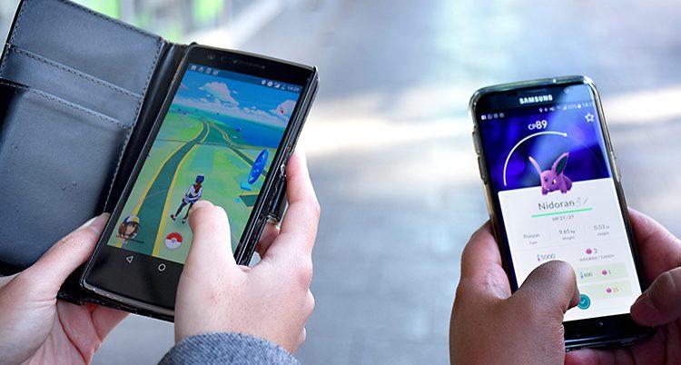 En hand med en mobil. Någon spelar ett spel.