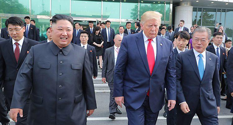 Kim och Trrump går bredvid varandra. Kim ler men Trump ser sur ut och tittar mot marken.