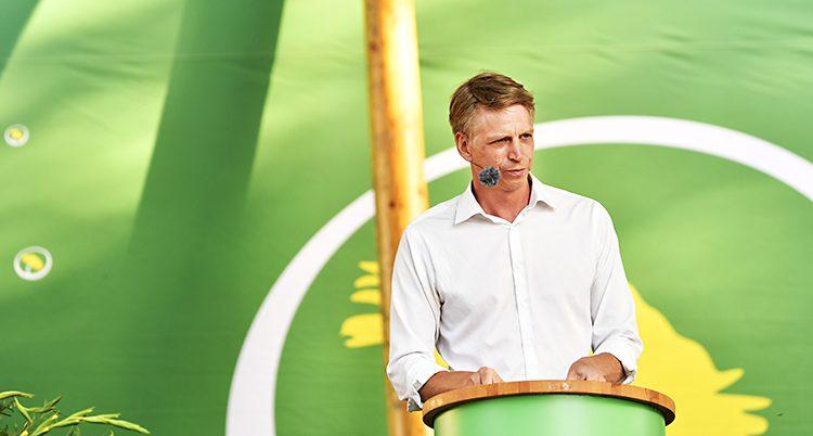 Miljöpartiets ledare Per Bolund står på en scen och håller ett tal.