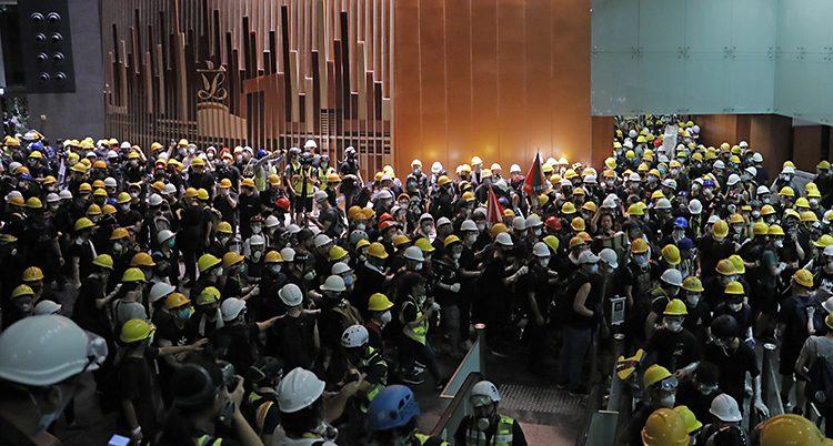 Människor i hjälmar trängs inn i riksdagens hus