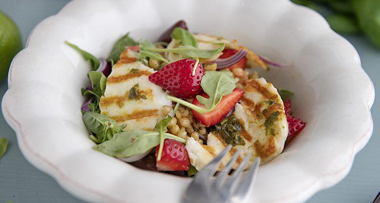 En tallrik med en snygg sallad med grillad och, röda jordgubbar och grön sallad