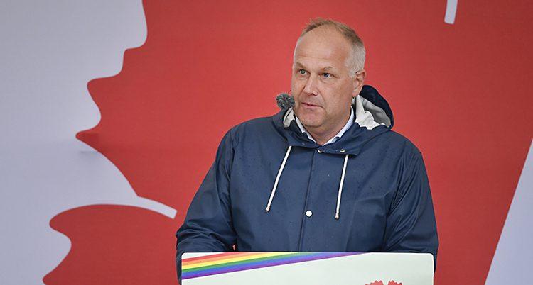 Jonas Sjöstedt står med regnjacka och håller ett tal på en scen.
