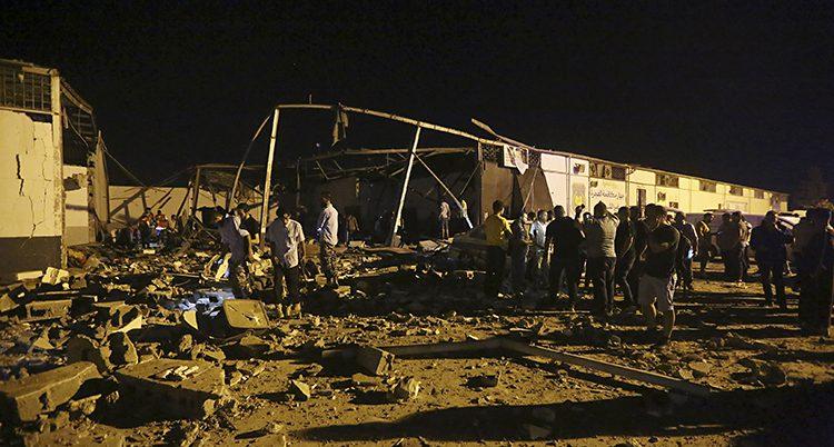 En bild tagen på natten. På abstånd är det människor som letar vid ett hus som är skadat av bomber.