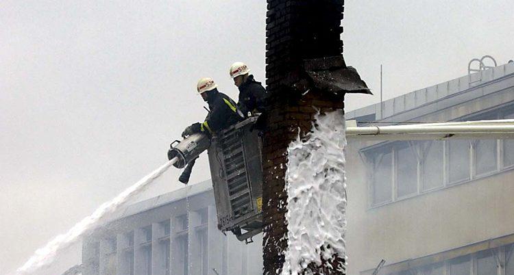 Två brandmän står i en korg i luften och sprutar skum på en brand.