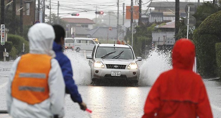 Människor tittar på en bil som kör så vattnet sprutar åt båda sidorna
