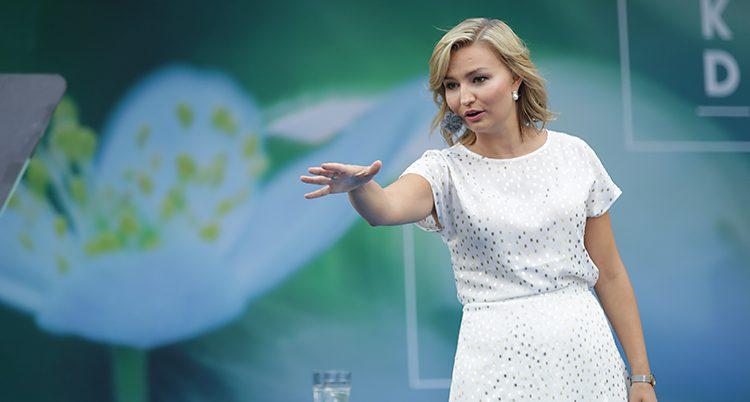 Ebba Busch Thor i vit klänning sträcker ut handen mot publiken.