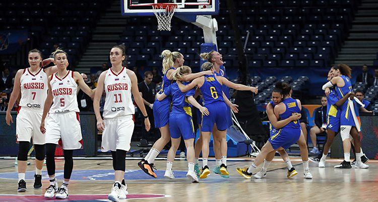 Några svenska spelare kramar varandra på en basketplan. Några ryska spelare ser ledsna ut.