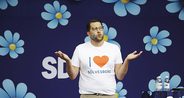 """Jimmie Åkesson står på en scen och pratar. Han har en t-shirt där det står """"I love Sölvesborg""""."""