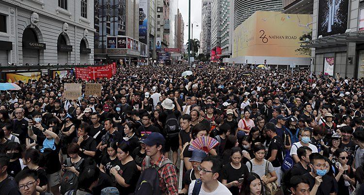 Människor trängs på en bred gata i Hongkong.