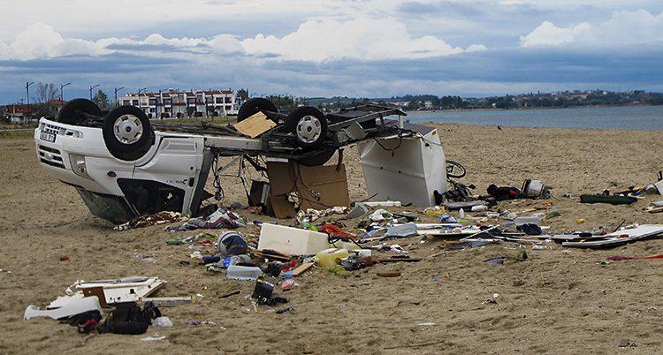 En bil ligger upp och ner på en strand. Omkring bilen ligger en massa saker.