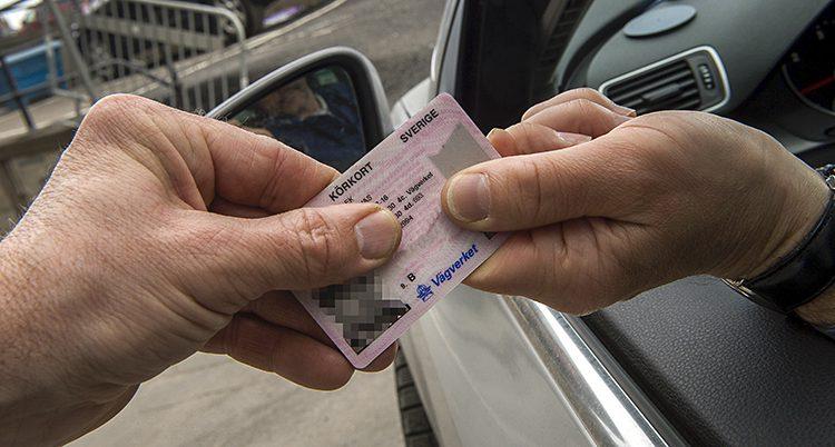 En person sitter i en bil och sträcker ut ett körkort. En annan hand tar emot körkortet.