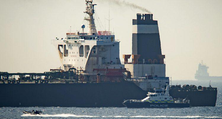 Ett stort fartyg i havet. Nära ligger en liten polisbåt.