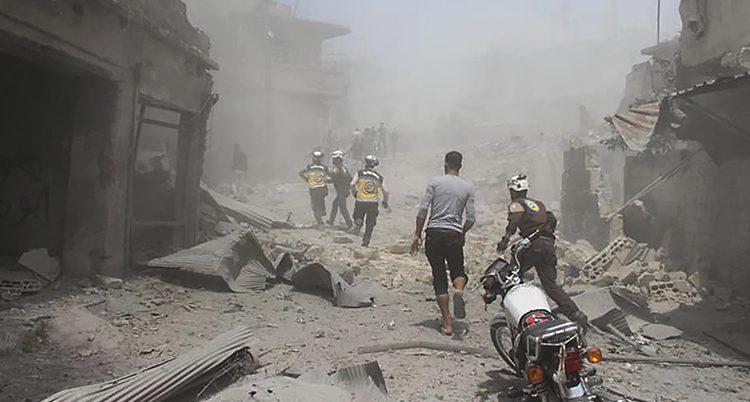 Människor i vita hjälmar rusar fram på en bombad gata full av damm.