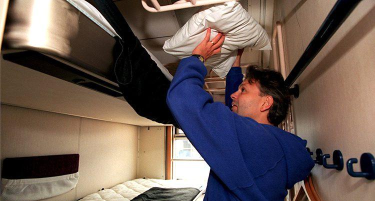 En man bäddar på en överslaf i en trång kupé.