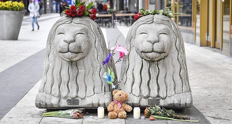 Två stora lejon i betong. Folk har lagt blommor bredvid och på lejonen.
