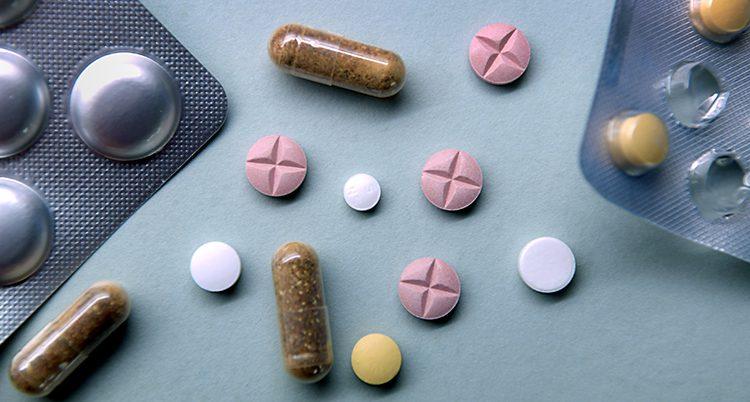 Några piller och kartor med tabletter som ligger på ett bord.