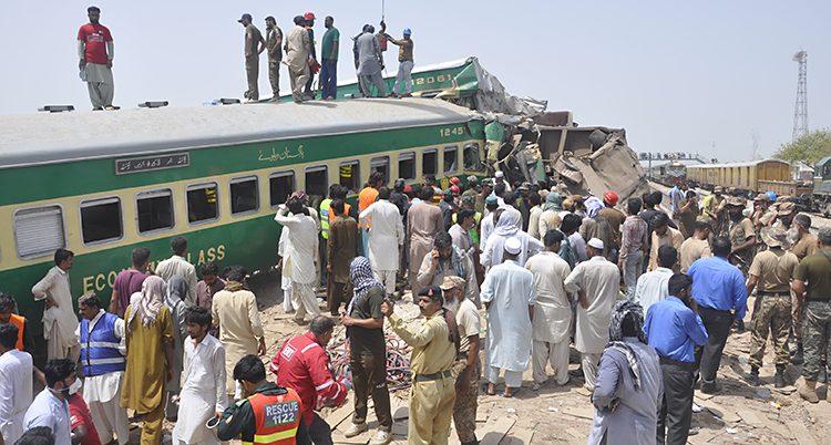 En massa människor står samlade vid ett tåg. Några människor står uppe på tåget.