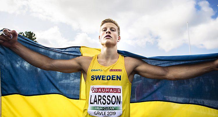 Friidrottaren Henrik Larsson håller en stor svensk flagga över ryggen.